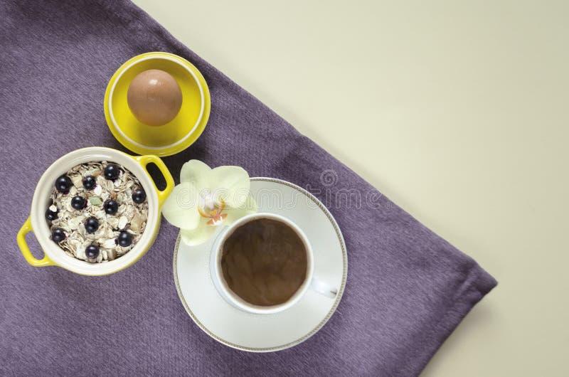 r 在燕麦粥,muesli用新鲜的蓝莓,鸡蛋,咖啡盘子的顶视图在一个黄色罐的用在紫色的牛奶 免版税库存照片