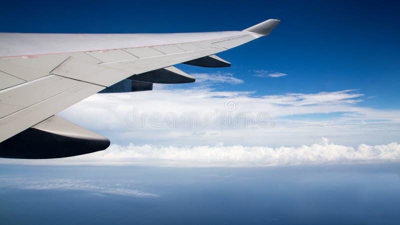 r 在飞行中平面翼 美丽的天空和美妙的云彩 库存照片