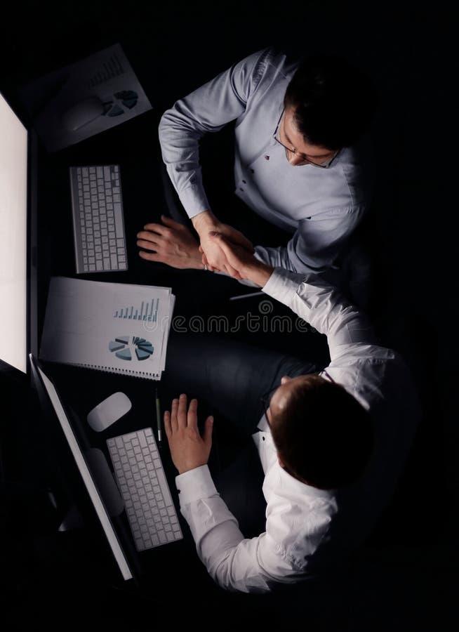 r 坐在书桌的握手同事 免版税库存照片