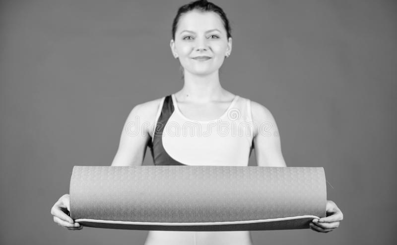r 女孩亭亭玉立的适合的运动员举行健身席子 i 舒展肌肉 r 库存图片
