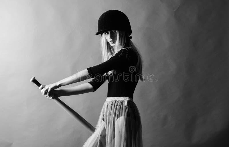 r 女孩嫩白肤金发的穿戴盔甲举行棒球棒红色背景 o 图库摄影
