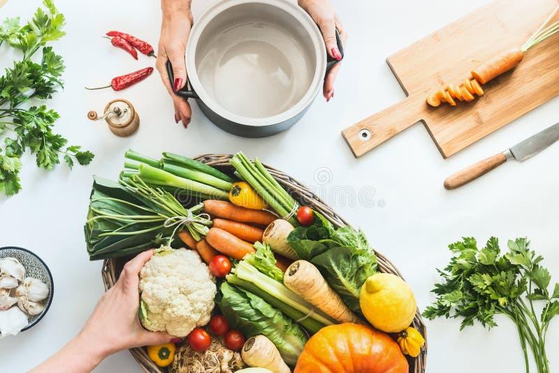 r 女性手准备在白色书桌背景的各种各样的五颜六色的有机农厂菜与烹调罐 库存图片