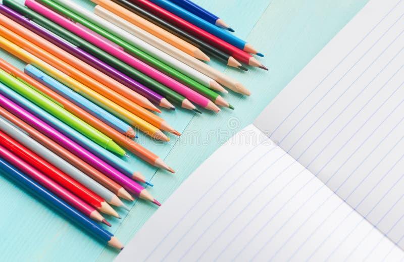 r 学校辅助部件,色的铅笔,与空的笔记本的笔在蓝色木背景 免版税库存图片