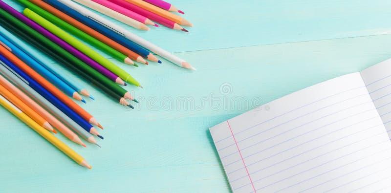 r 学校辅助部件,色的铅笔,与空的笔记本的笔在蓝色木背景 库存照片