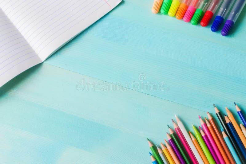 r 学校辅助部件,色的铅笔,与空的笔记本的笔在蓝色木背景 图库摄影