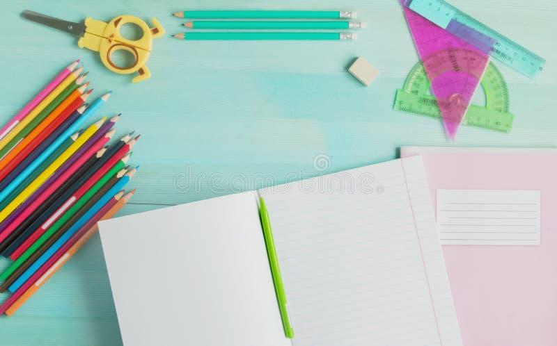 r 学校辅助部件,色的铅笔,与空的笔记本的笔在蓝色木背景 免版税库存照片