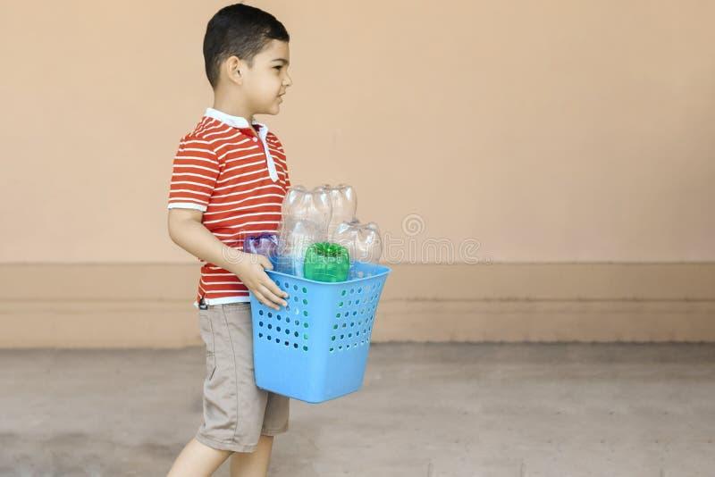 r 小男孩收集了塑料瓶和拿着回收站 ?? 免版税库存照片