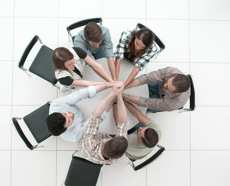 r 微笑的企业队一起折叠了他们的手 免版税库存照片