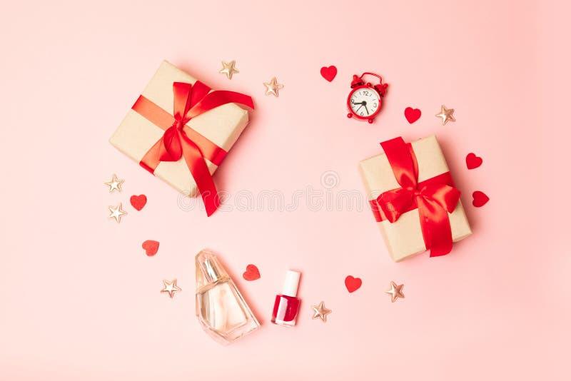 r 惊奇有一把红色丝带弓、指甲油和一个红色时钟的礼物盒在与地方的桃红色背景 免版税库存照片