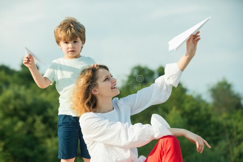 r 愉快的使用在蓝色夏天天空的母亲和小儿子 幸福家庭-母亲和孩子草甸的有a的 库存照片