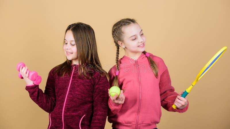 r 愉快的孩子用运动器材 e ?? 健身杠铃 青少年的女孩健身房锻炼  图库摄影