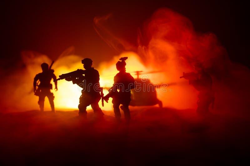 r 战士在沙漠在与战斗直升机或直升机攻击专辑的军事行动时 库存图片