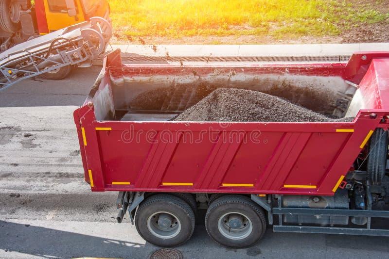 r 折除沥青路面 被回收的沥青面包屑倾吐在传送带入卡车身体 免版税库存照片