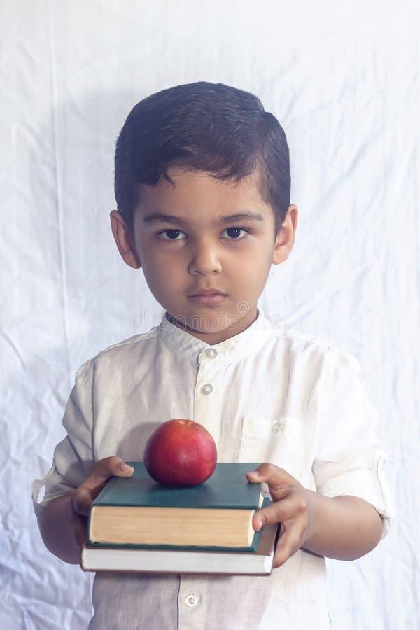 r 拿着堆书的逗人喜爱的中东男孩反对白色背景 画象中亚 免版税库存图片