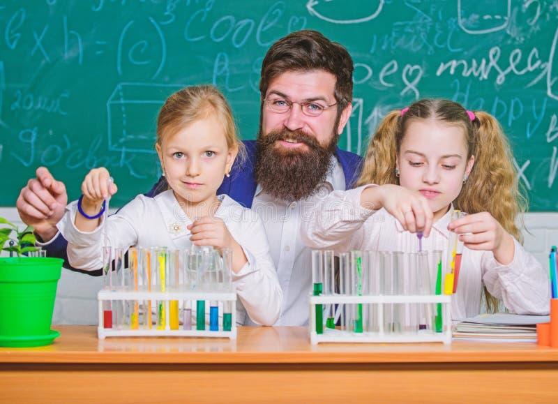 r 拿着试管的女小学生引导的是由老师 执行实验的小学生在科学 免版税库存图片