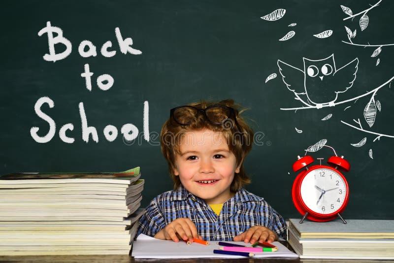 r 指向在黑板的滑稽的小男孩 一点学生男孩满意对一个优秀标记 ?? 库存图片