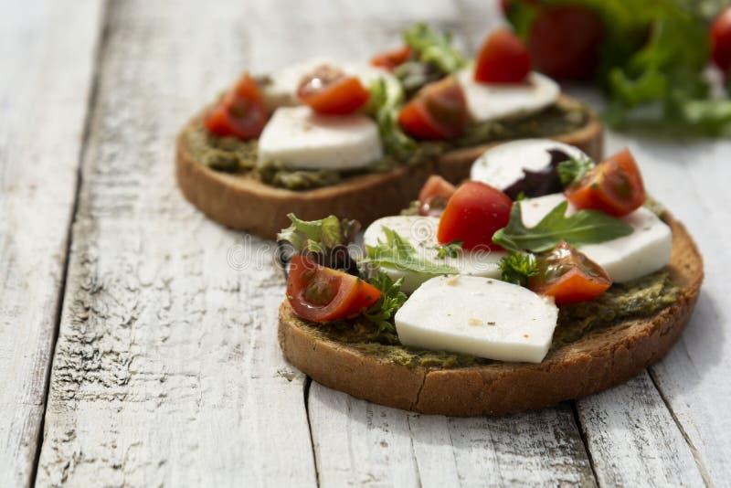 r 敬酒三明治用无盐干酪、西红柿和pesto,轻的木背景 r ?? 库存图片