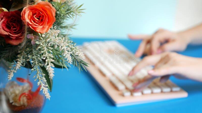 r 时髦的招呼的显示卡 女性手在一个桃红色键盘键入,在花旁边 在蓝色 库存照片