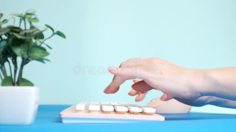 r 时髦的招呼的显示卡 女性手在一个桃红色键盘键入,在花旁边 在蓝色 免版税库存照片