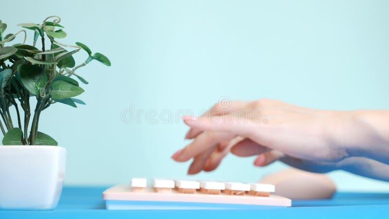 r 时髦的招呼的显示卡 女性手在一个桃红色键盘键入,在花旁边 在蓝色 免版税图库摄影