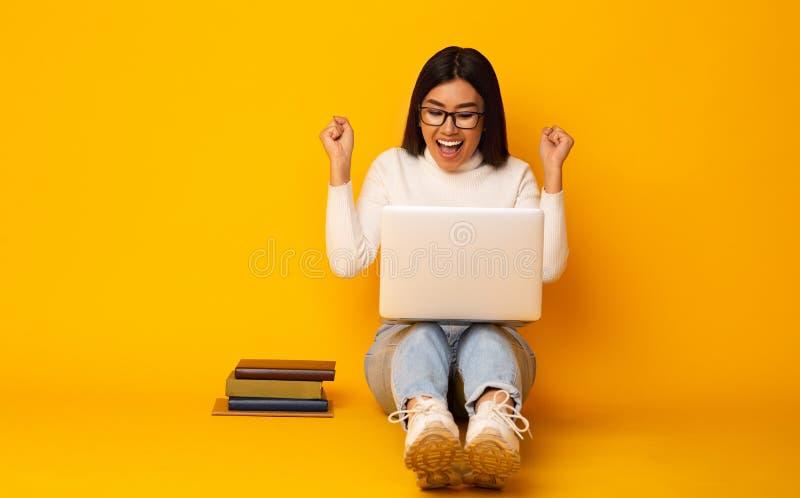 r 有书和膝上型计算机的,黄色背景愉快的学生女孩 免版税图库摄影