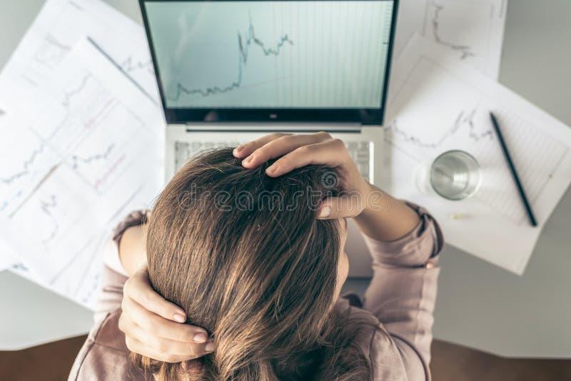 r 有头疼的疲倦的在图表和图背景的女商人在有杯的办公室水和药片打印 图库摄影