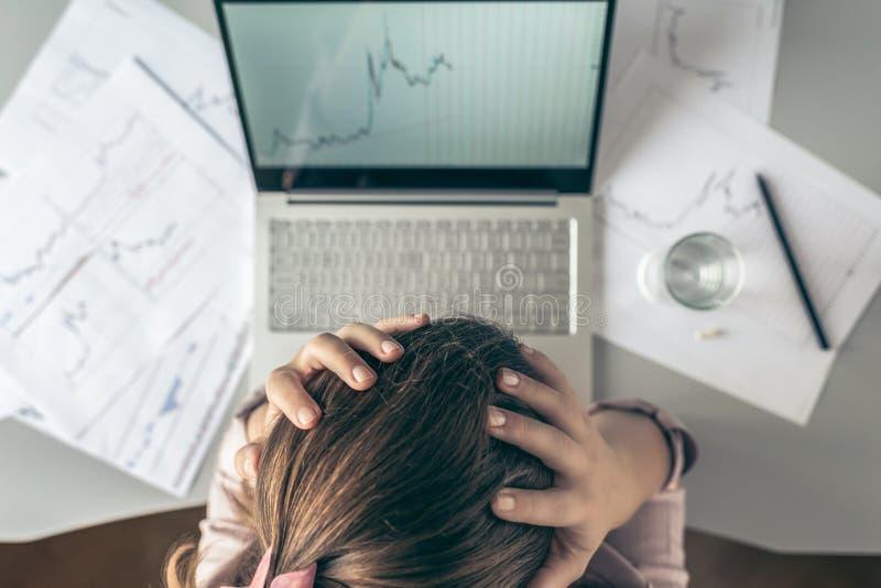 r 有头疼的疲倦的在图表和图背景的女商人在有杯的办公室水和药片打印 免版税库存图片