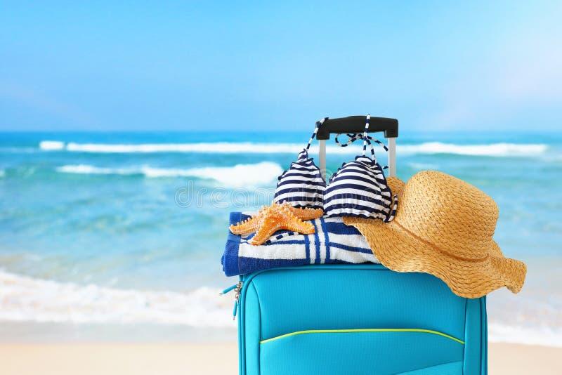 ?? r 有女性帽子、海星、比基尼泳装和海滩毛巾的蓝色手提箱在热带背景前面 免版税库存图片