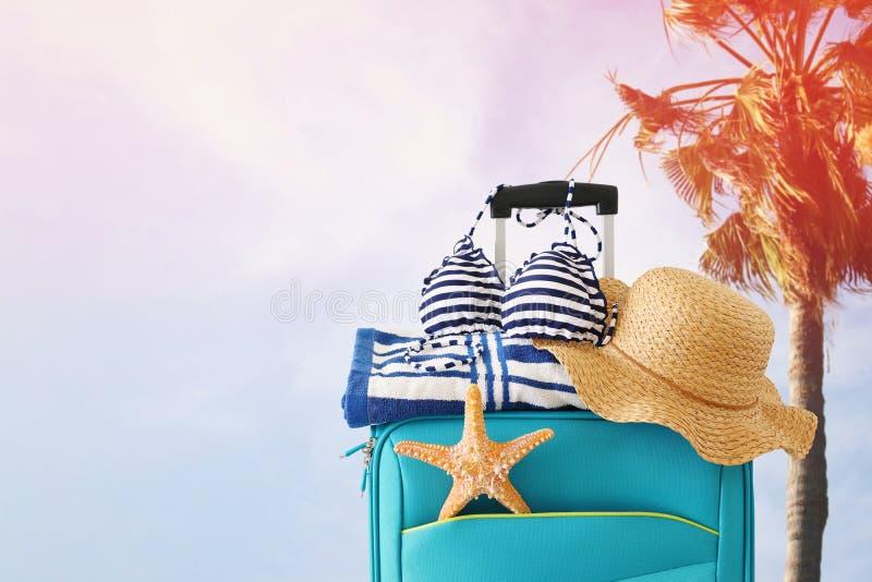 ?? r 有女性帽子、海星、比基尼泳装和海滩毛巾的蓝色手提箱在热带背景前面 库存照片