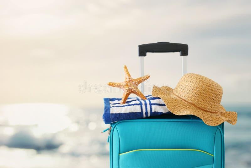 ?? r 有女性帽子、海星和海滩毛巾的蓝色手提箱在热带背景前面 免版税库存照片