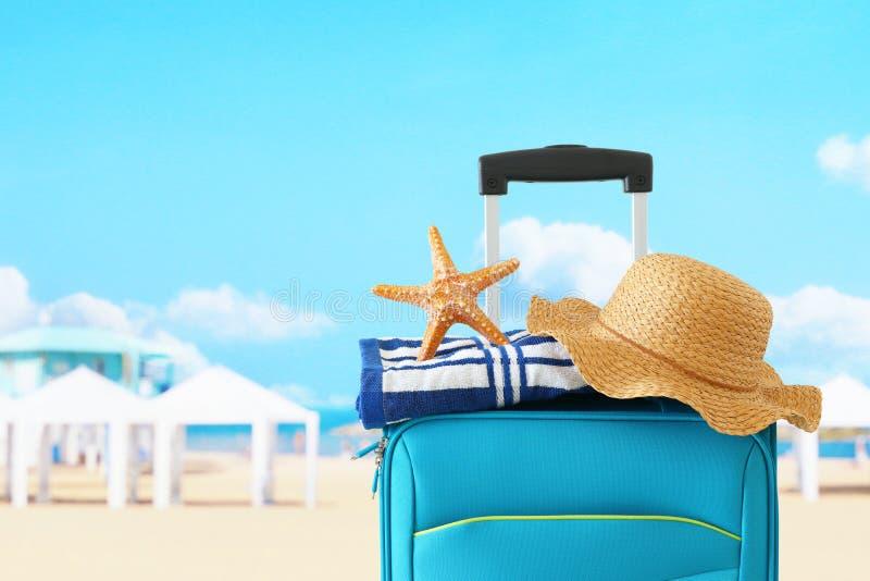 ?? r 有女性帽子、海星和海滩毛巾的蓝色手提箱在热带背景前面 免版税库存图片