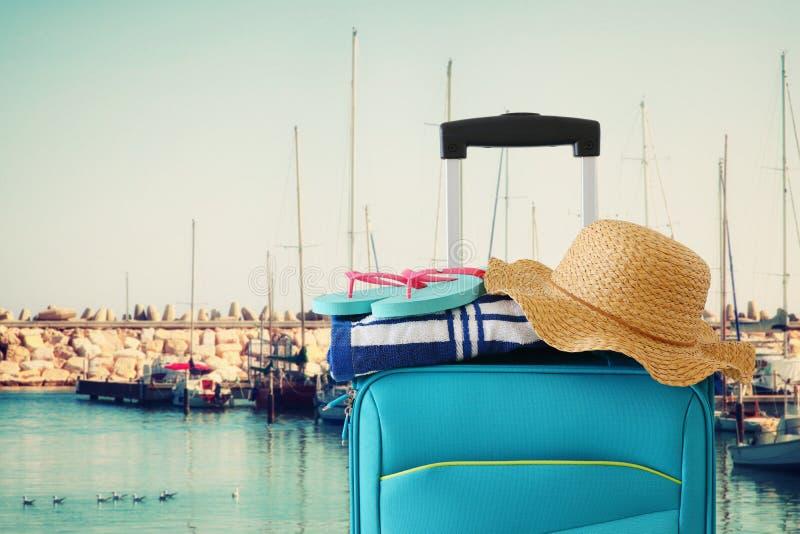 ?? r 有女性帽子、轻碰轻碰和海滩毛巾的蓝色手提箱在小游艇船坞前面有游艇背景 库存照片