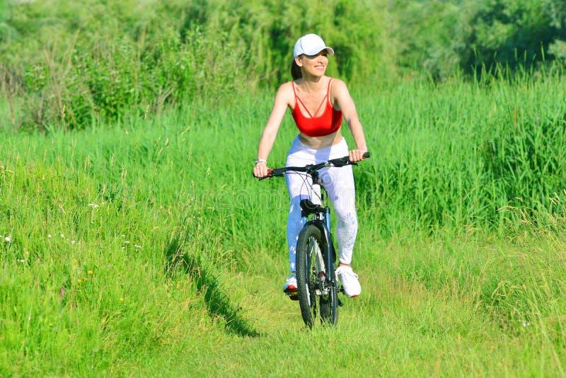 r 有完善的微笑的俏丽的妇女在公园草甸骑自行车 免版税库存图片