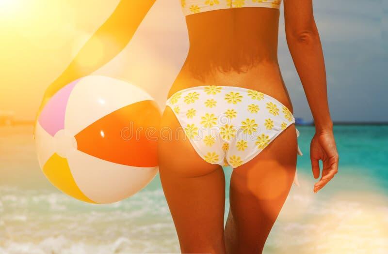 r 有球的性感的妇女在蓝色海和多云天空背景,在海滩背景的含沙妇女屁股 库存照片