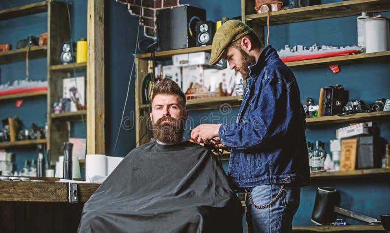 r 有用海角盖的胡子的行家服务由专业理发师在时髦的理发店 繁忙的理发师 图库摄影
