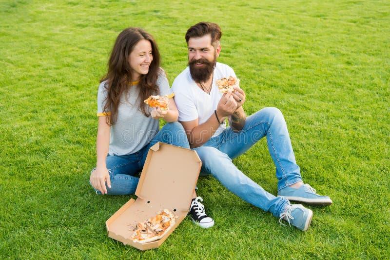 r 有胡子的男人和妇女享用低贱比萨 结合在约会户外用比萨的爱 饥饿的学生 免版税库存图片