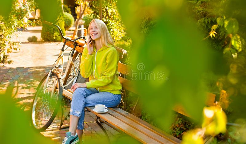 r 有自行车的活跃女孩 行动和能量 有自行车的妇女在开花的庭院里 免版税库存图片