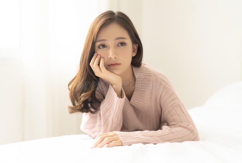 r 温暖的被编织的桃红色衣裳的年轻美丽的亚裔妇女在家 ?? ????? 免版税库存图片