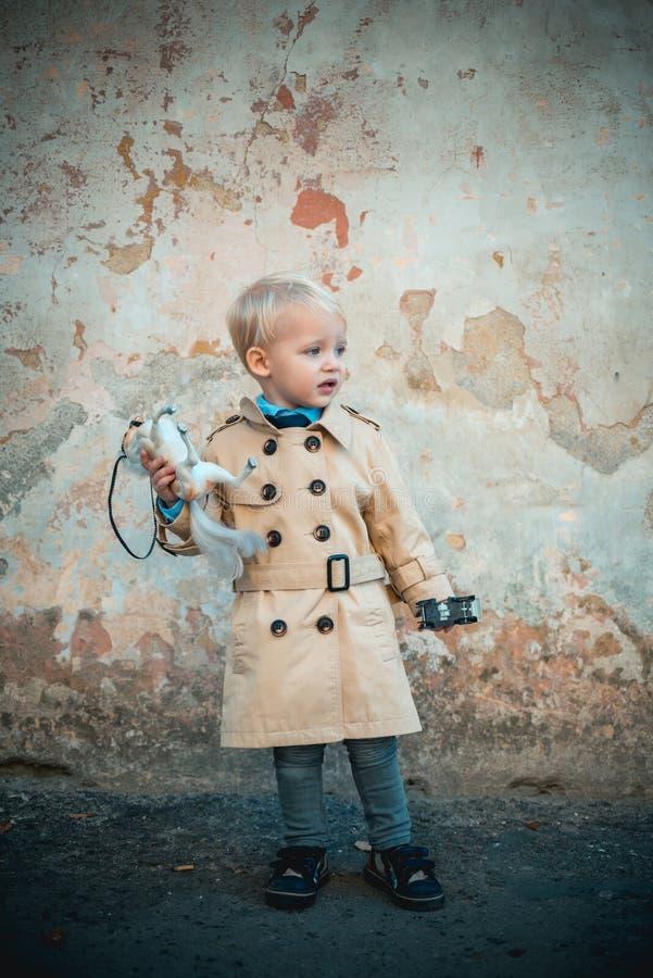r 演奏玩具 与玩具马和汽车的小孩子 E o 葡萄酒外套的小男孩 免版税库存图片