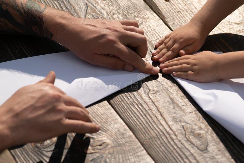 r 父亲和儿子做一架纸飞机 r 一起时间 家庭爱好 父亲教儿子 免版税库存图片
