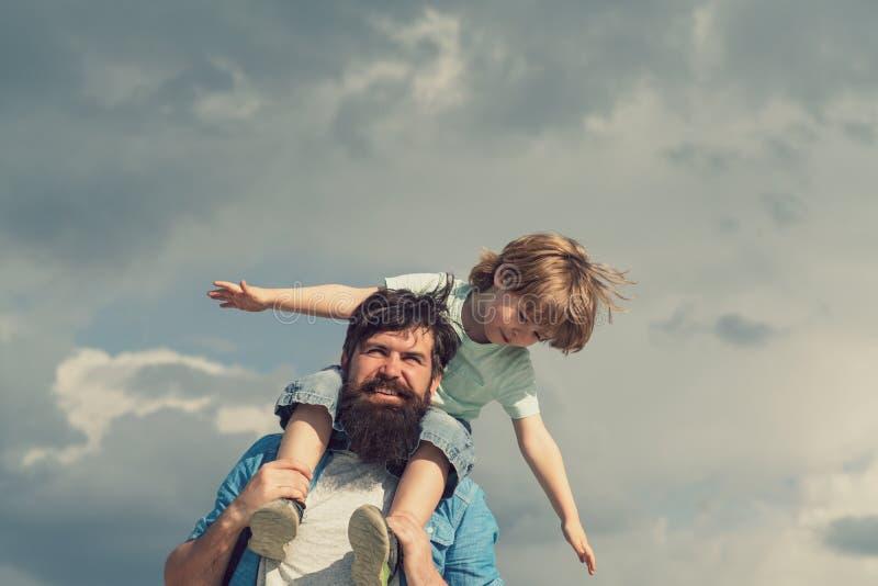 r r 爸爸和儿童儿子 使用愉快的孩子-飞机 给儿子的愉快的父亲画象 免版税图库摄影