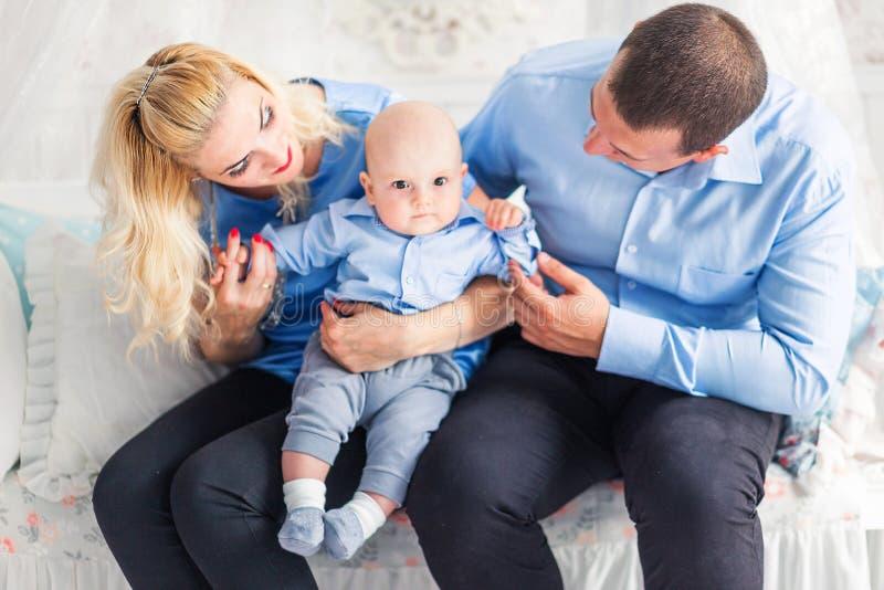 r 爸爸和妈妈坐有他们的年轻儿子的长沙发 免版税库存图片