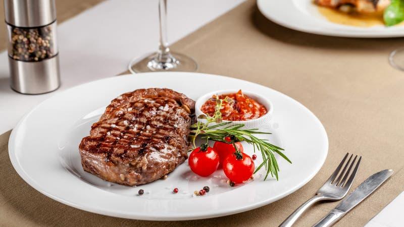 r 牛排用红色bbq西红柿酱和西红柿 r 在一块白色板材的大盘子 免版税库存图片