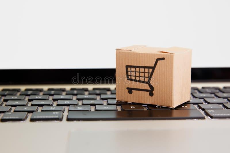 r 电子商务和送货服务概念:有一个推车或台车商标的纸箱在膝上型计算机 免版税库存照片
