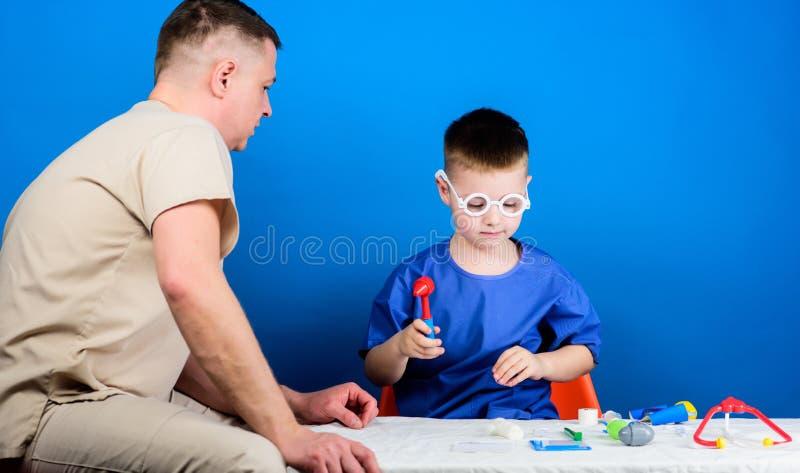 r 男孩逗人喜爱的孩子和他的父亲医生 医院工作者 E r E 免版税库存图片