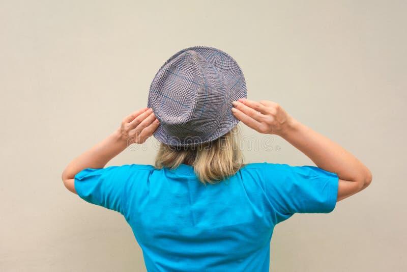 r 白色中部变老了妇女逗留回到我们并且接触她的帽子的挡水板 没有面孔的后面看法 免版税库存照片
