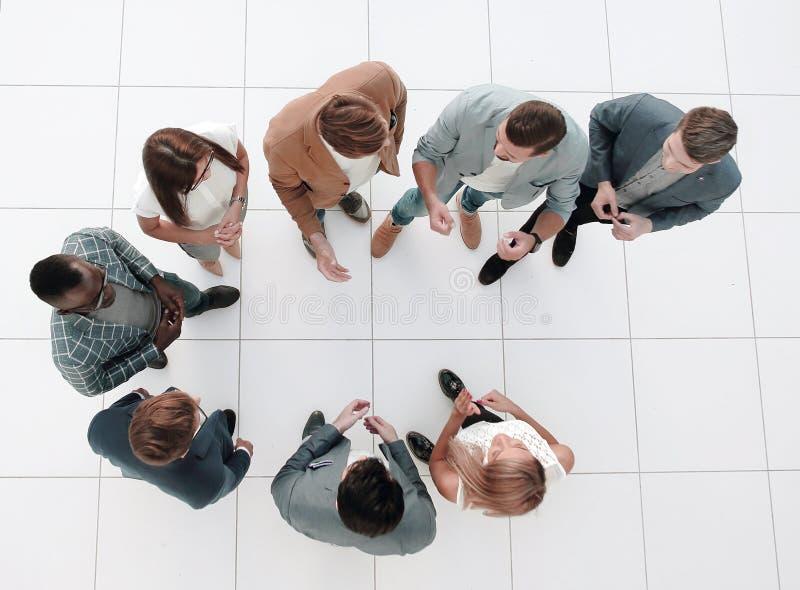 r 站立在办公室的大厅的一雇员小组 免版税库存图片