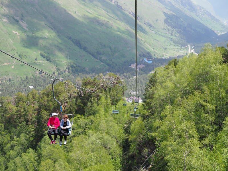 r 结合徒步旅行者或游人享受升降椅滑雪电缆车和美好的山夏天风景乘驾  免版税库存照片
