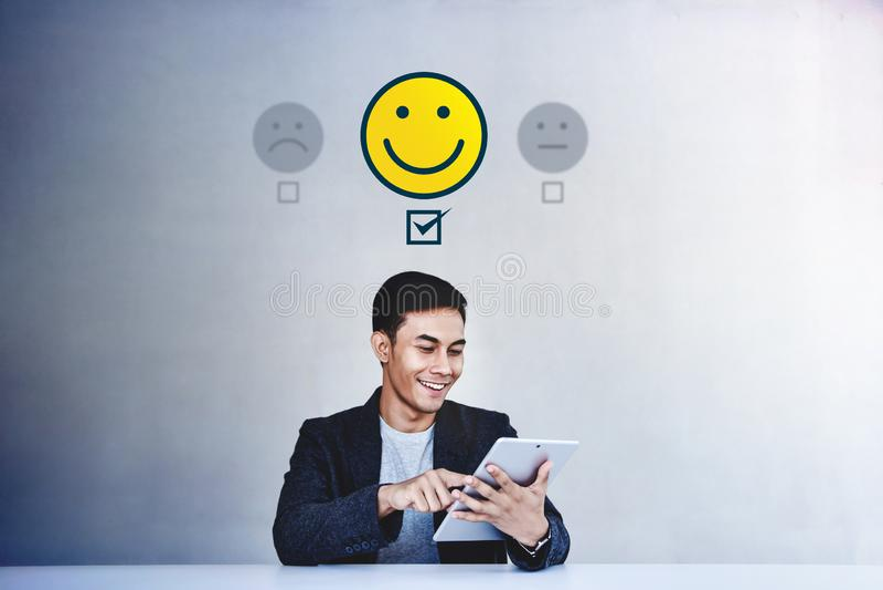 r 给他的在满意网上调查的年轻商人正面回顾 愉快的客户 库存照片