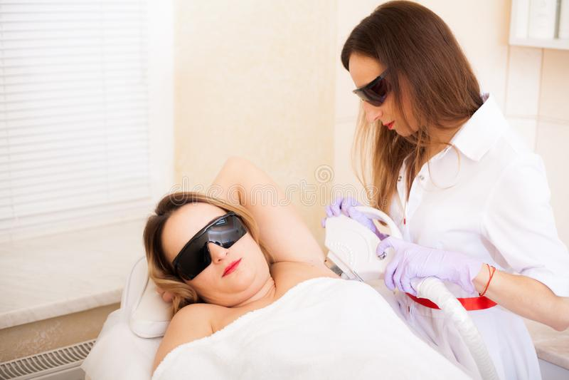 r 美女在风镜的从激光辐照区域,医生的手一名美容师办公室在 库存照片